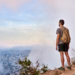 Full length shot of a young male hiker standing on a mountain trail looking through the clouds at the city below